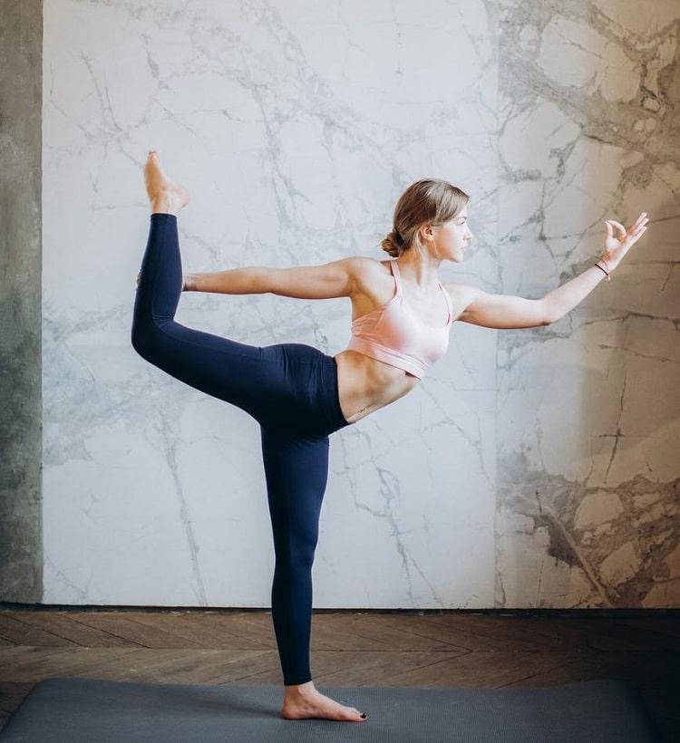 A woman doing Natarajasana or Dancer's Pose on a dark gray yoga mat inside a fitness studio.