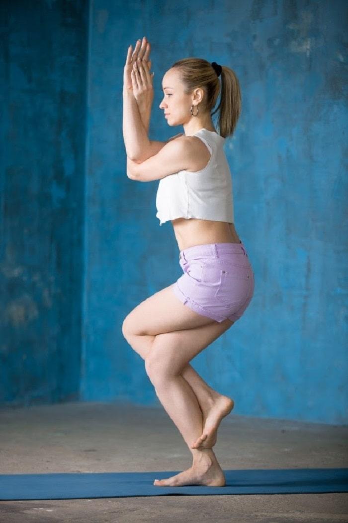 A woman doing Garudasana or Eagle Pose on a blue yoga mat inside a fitness studio.