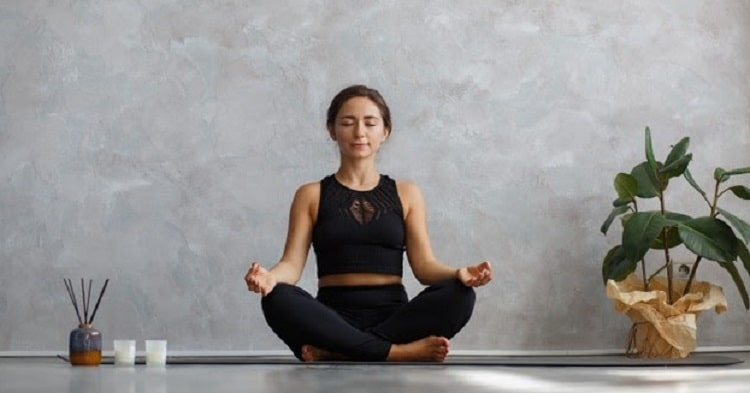 A woman doing Sukhasana or Easy Pose on a dark gray yoga mat, with some incense and candles on the side.
