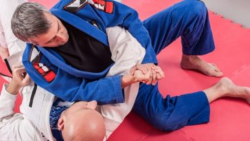 Brazilian Jiu-Jitsu (BJJ) instructor demonstrates ground fighting arm to student.