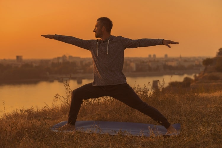 A man in a gray hoodie doing Warrior 2 pose on a blue yoga mat outdoors.
