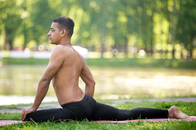 A man doing a yoga recovery pose on a purple yoga mat outdoors.