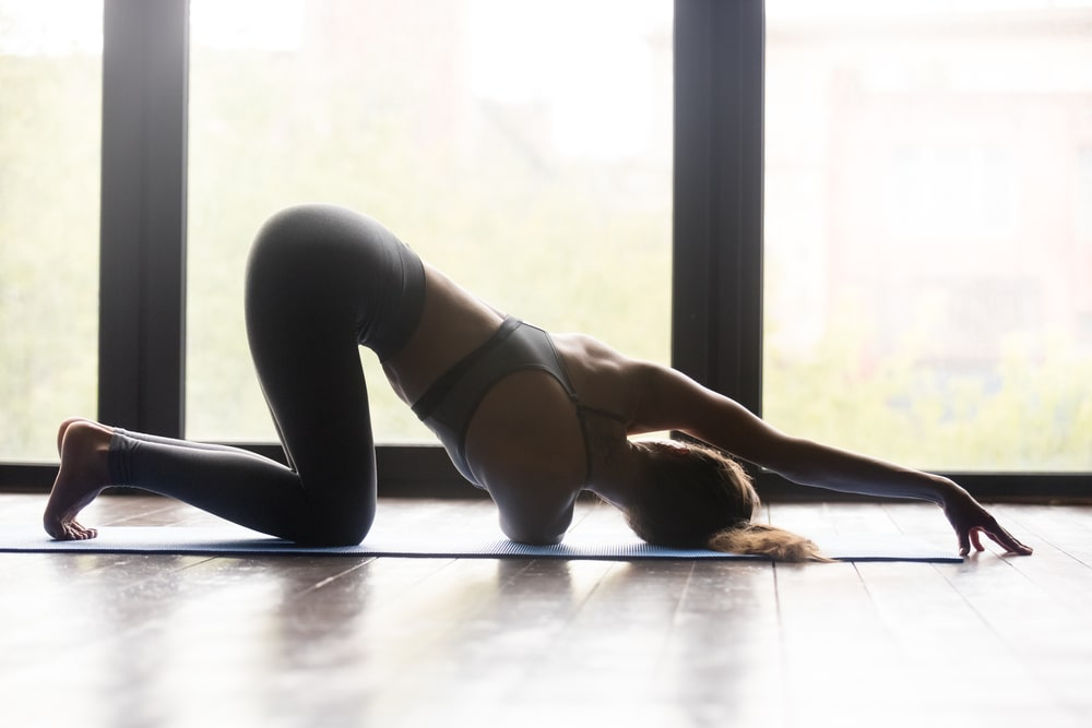 A woman wearing a pair of high-quality black yoga pants, doing Thread the Needle Pose for her yoga routine on a yoga mat indoors.