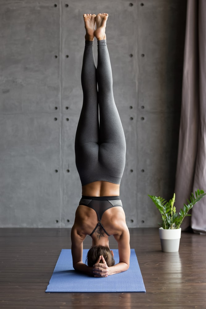 A woman wearing a pair of high-quality gray yoga pants, doing Headstand for her yoga routine on a blue yoga mat indoors.