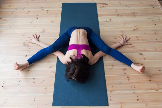 A female yogi practicing Kurmasana or Tortoise Pose in a high-quality violet sports top and royal blue leggings made of durable stretch fabric.