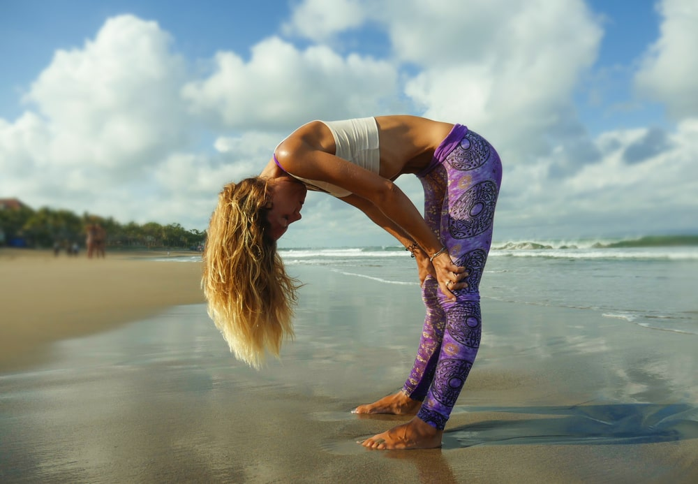 A woman in a white sports top and printed yoga pants, practicing uddiyana bandha at the beach as part of her yoga routine.