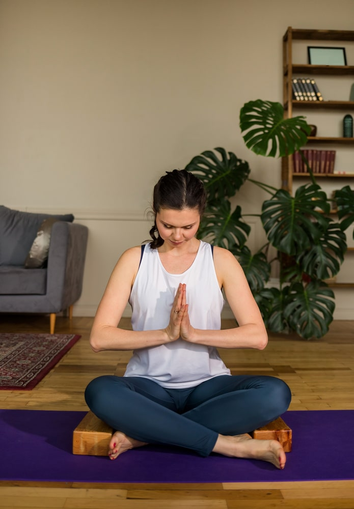 A woman in Lotus Pose with praying hands, seated on a yoga cushion, while practicing jalandhara bandha or the throat lock for her yoga routine.
