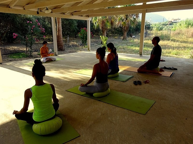 Yogis meditating on their green cushions for yoga class, with the instructor guiding them.