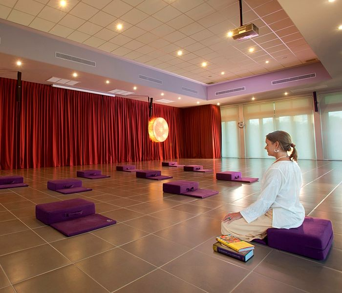 A female yoga instructor seated on a purple-colored, rectangular-shaped meditation pillow with her eyes closed, doing a meditative exercise before her yoga class starts.