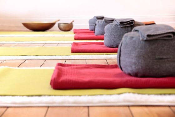 Gray-colored, circular-shaped meditation cushions, along with blankets and mats neatly arranged for a yoga class.