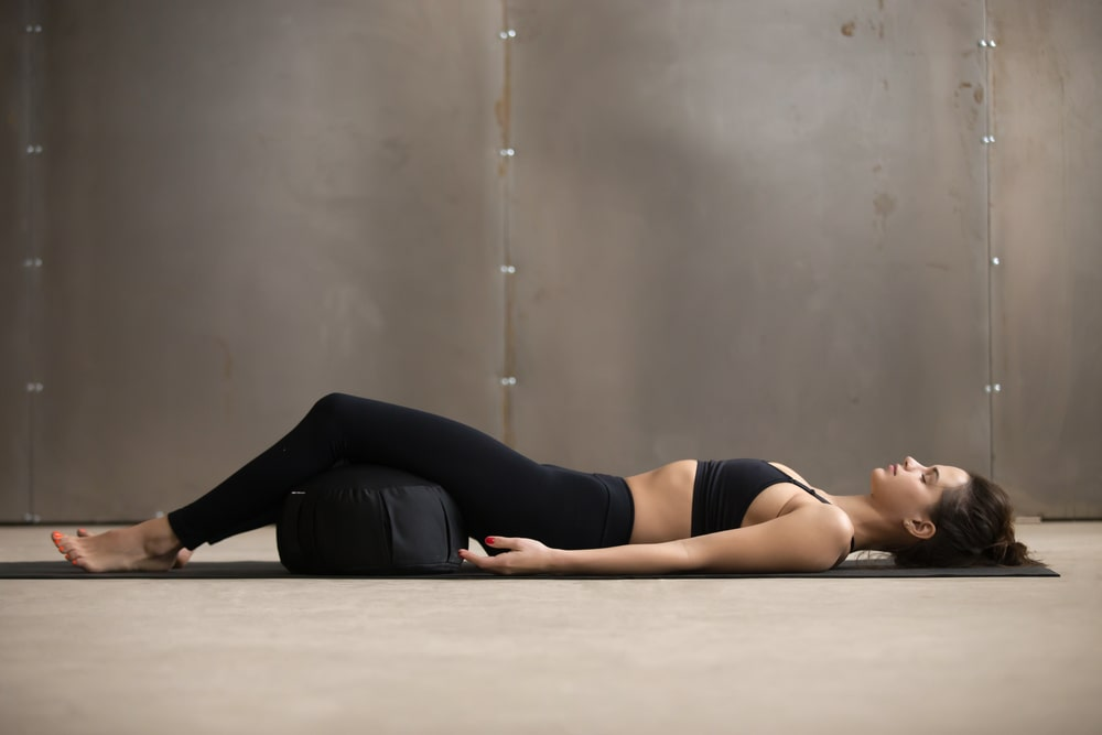 A woman doing Corpse Pose using a meditation cushion to prop up her legs and support her lower back.