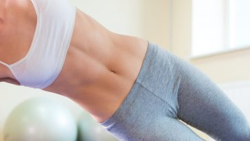 A close-up shot of a woman's well-defined abs while doing Side Plank Pose in a white sports top and gray yoga pants.