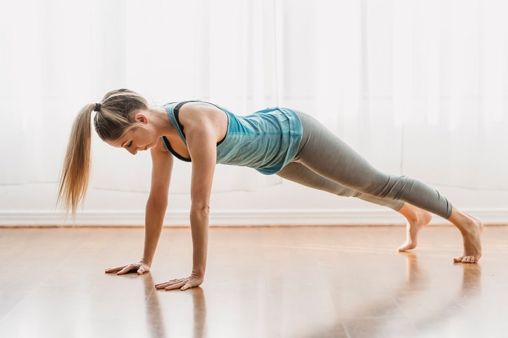 A woman doing Plank Pose on a bare floor with white curtains in the background.