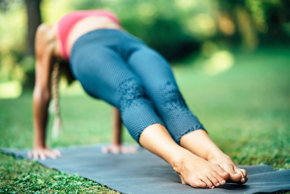 A woman in a pink sports top and blue yoga pants doing yoga outdoors, holding her Reverse Plank Pose.