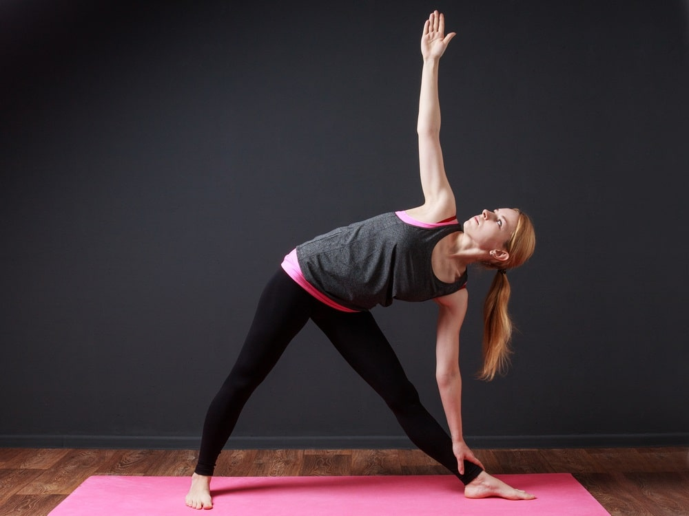 A woman in a layered pink and gray top and black yoga pants, holding her Triangle Pose on a pink yoga mat.