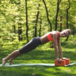 A woman practicing yoga outdoors using two orange blocks.