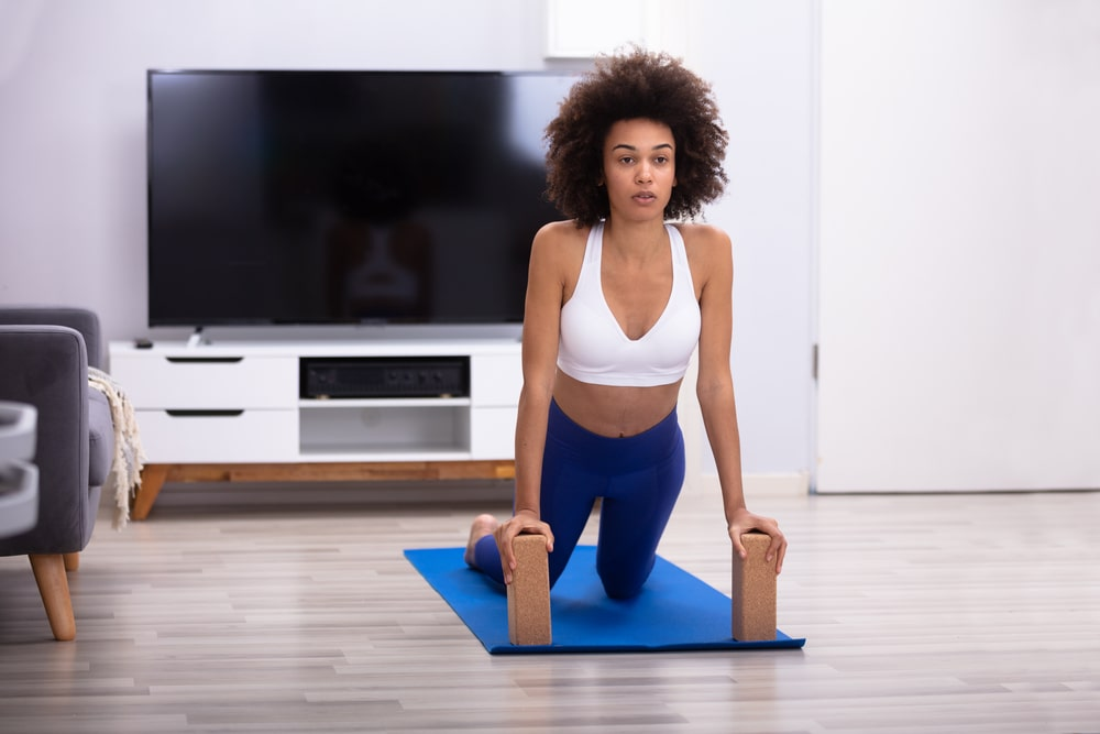 A woman practicing yoga on a blue yoga mat in the living room, with two brown yoga blocks supporting her weight.