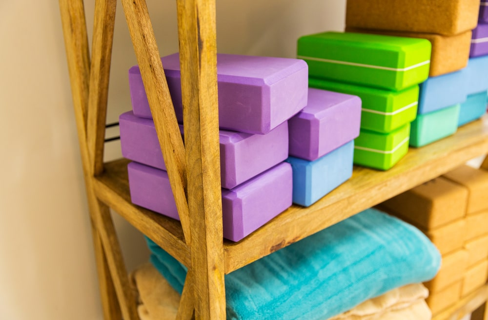 A wooden rack with stacked up yoga blocks of various colors.