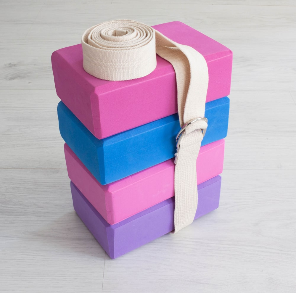 A stack of various colors of same-size yoga blocks tied by a cream-colored yoga strap.