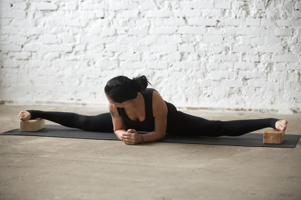 A woman doing an advanced yoga pose with her legs stretched apart and both feet resting on separate yoga blocks.