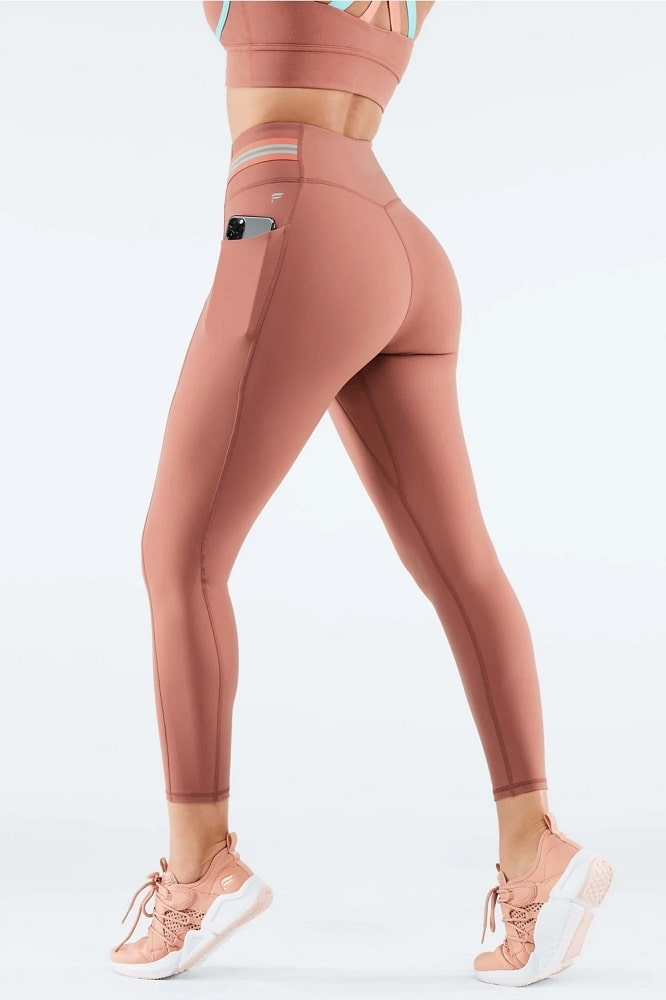 A salmon-colored high-waisted Motion365® with breathable compression with side pockets from Fabletics.