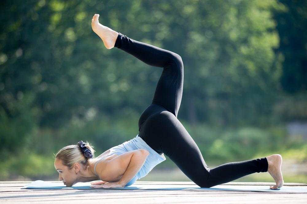 A woman doing Ashtanga Namaskara for her outdoor yoga routine, wearing a pair of black high-quality yoga pants.