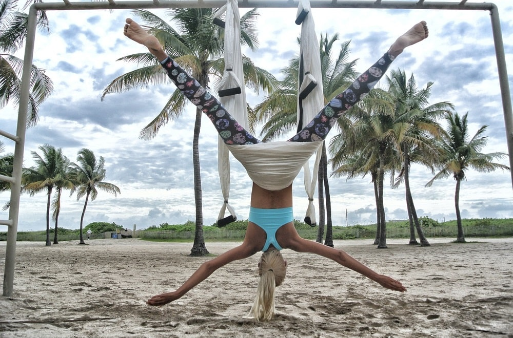 A woman wearing printed yoga pants and a blue top, doing her anti-gravity yoga routine using a white yoga swing by the beach.
