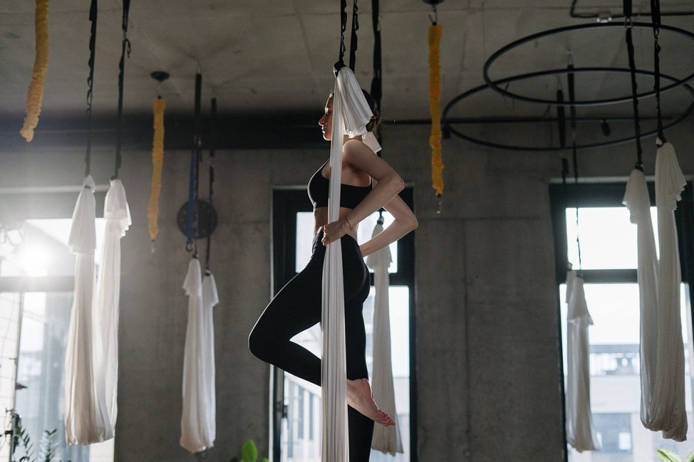 A woman wearing black yoga pants and matching top, doing her anti-gravity yoga routine using a white yoga swing at an indoor studio.