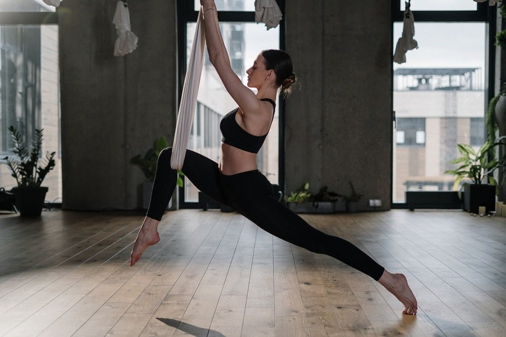 A woman wearing black yoga pants and matching top, doing her anti-gravity yoga routine from a white durable yoga swing carefully tied to the ceiling.
