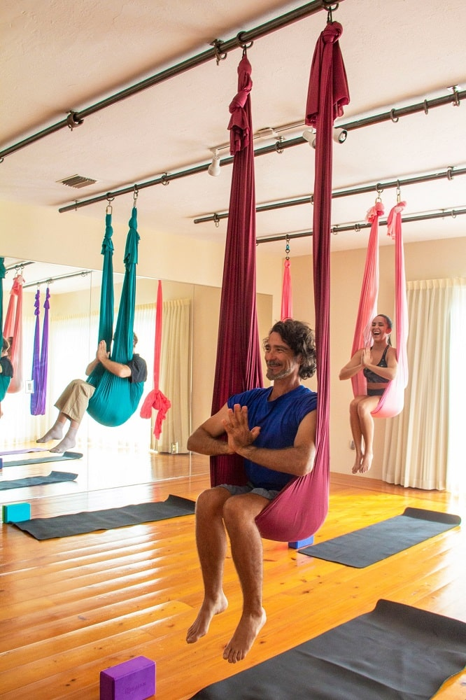 A male yoga instructor guiding his yoga students during an anti-gravity yoga class, with various colors of yoga swings safely suspended from the ceiling.