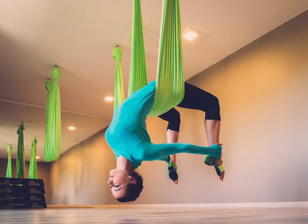 A female yogi suspended by a green-colored yoga swing tied securely to the ceiling of an indoor yoga studio.