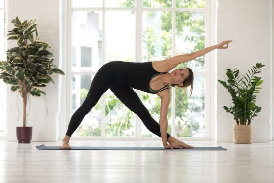 A woman standing in Tree Pose, wearing a comfortable pair of black stretch yoga pants and matching top.