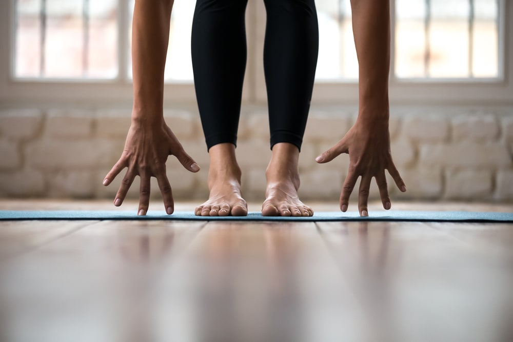 A woman doing yoga in a comfortable pair of black stretch yoga pants, with her feet together and hands touching the ground.