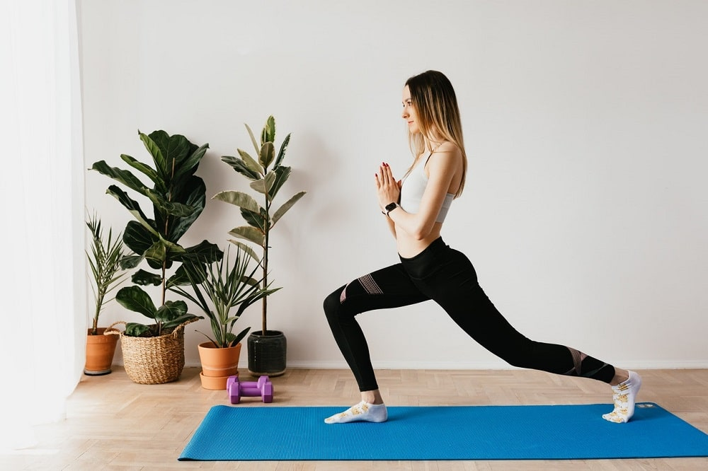 A woman in Crescent Lunge with praying hands, wearing a comfortable pair of black stretch yoga pants.