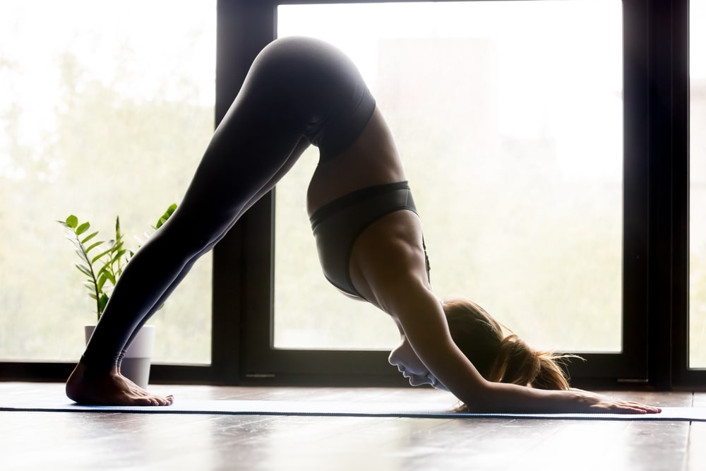 A woman doing Downward-Facing Dog, wearing a comfortable pair of dark gray stretch yoga pants.