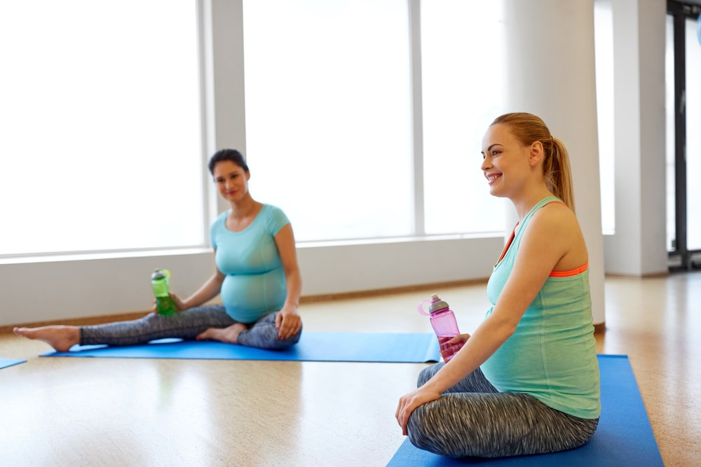 Two prenatal yoga students taking a short break from class, each holding a water bottle in their hands.