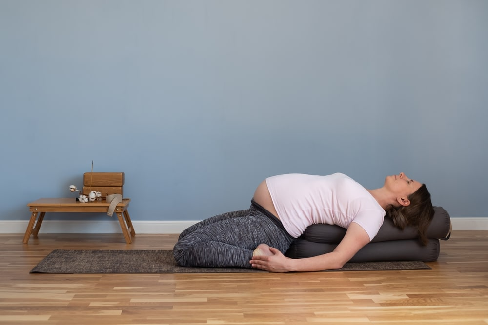 A pregnant woman on her third trimester doing a restorative yoga pose assisted by pillows propping up her back.