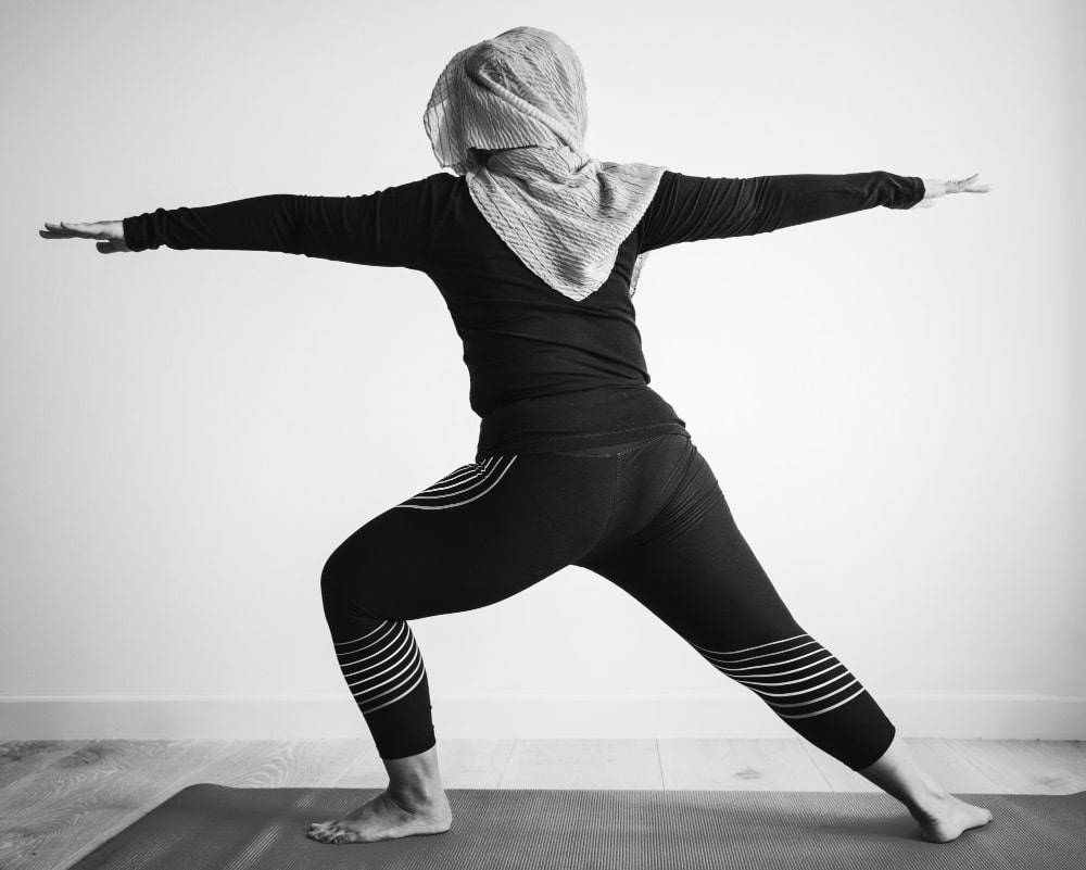 A black and white photo of an Islamic woman doing Warrior Pose 2 on a yoga mat.