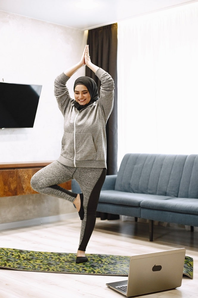 An Islamic woman wearing a hoodie and yoga pants while doing Tree Prose on a printed yoga mat in the living room.