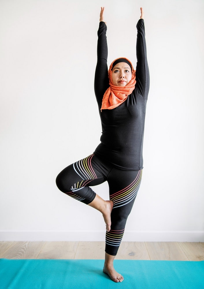 An Islamic woman doing Tree Pose with her arms raised on a turquoise-colored yoga mat.