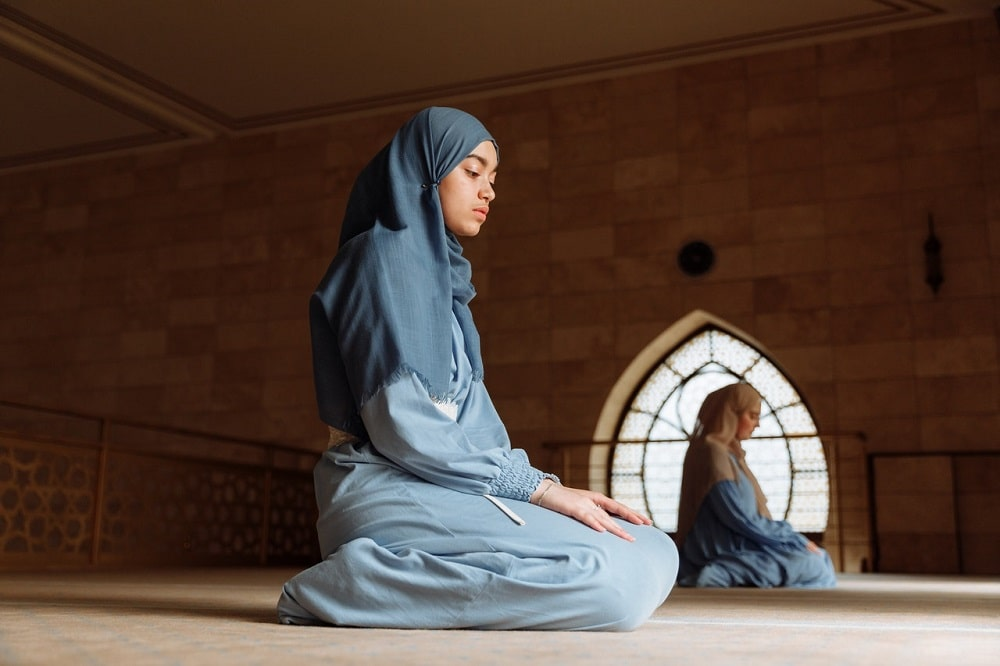 Two Islamic women seated far apart, eyes open and praying inside a temple.