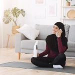A Muslim woman talking on her cellphone with a water bottle in hand, sitting on a gray yoga mat in the living room after her workout.