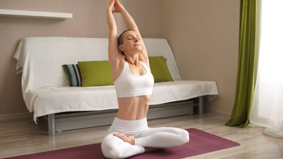 A sporty female wearing matching high-quality white yoga activewear and stretching in Lotus Pose on her maroon-colored yoga mat in the living room.