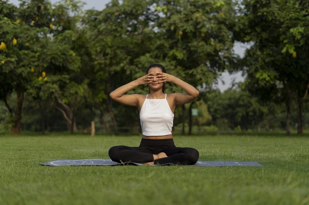A woman feeling relaxed and focused while doing Bhramari pranayama on her yoga mat placed on a grassy lawn, with foliage in the surrounding area.