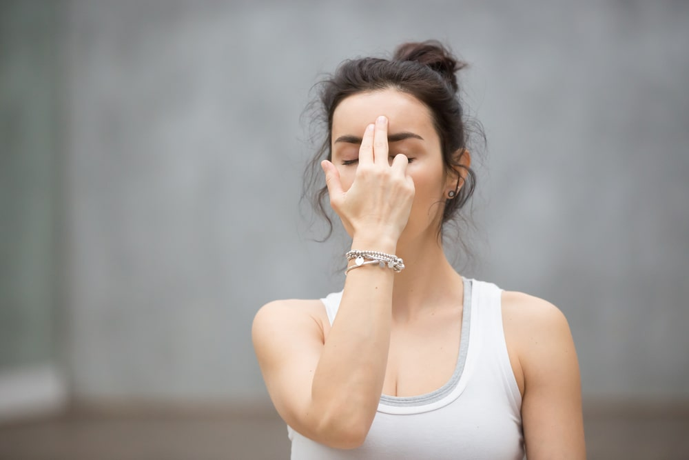 A woman in a white and gray tank top doing alternate nostril breathing as part of her morning yoga routine.