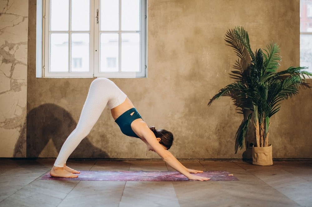 A female yogi in a light-colored yoga pants and navy blue sports top, doing Downward-Facing Dog on printed yoga mat.