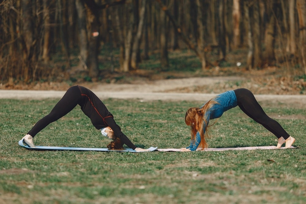 Two female yogis practicing Downward Dog together on their yoga mats outdoors, feeling the benefits of the pose on their muscles.