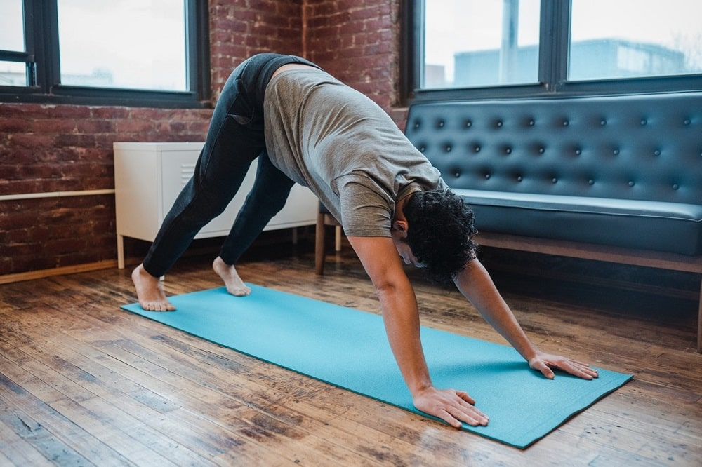 A guy doing Downward-Facing Dog with heels lifted on a bright blue yoga mat indoors.
