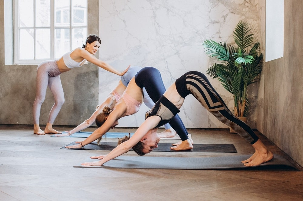 A female yoga instructor guiding her students to properly achieve Downward-Facing Dog during their yoga class indoors.