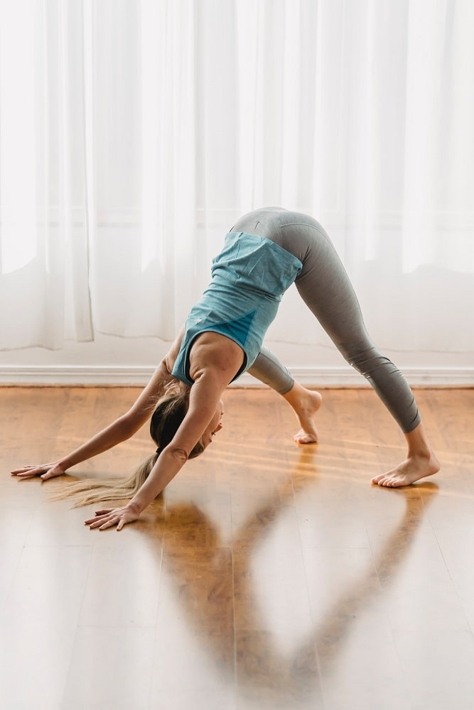 A female yogi wearing gray yoga pants and a blue tank top, doing Downward-Facing Dog on a bare wooden floor right by the window with sheer white curtains.